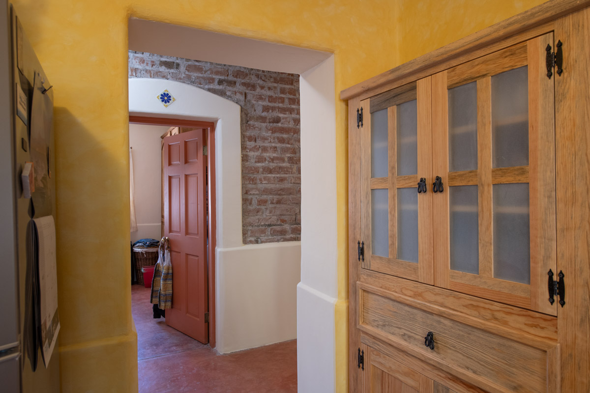 Beautifully restored four bedroom adobe home kitchen looking into hallway